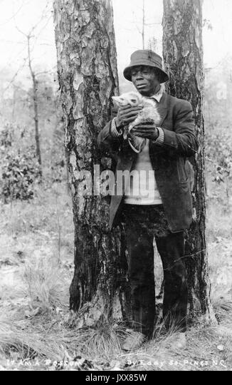 A mature African American wearing a hat and and coat stands in a wooded area looking at a dead possum that he holds - Stock Image