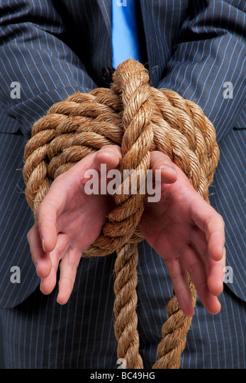 Close up of a businessmans hands tied with rope - Stock Image