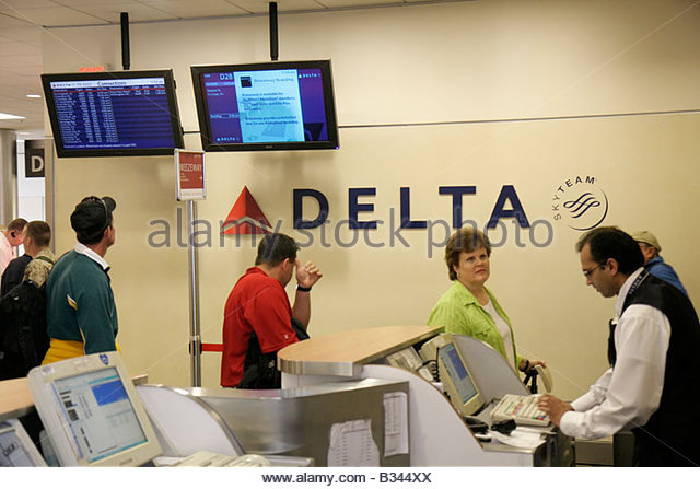 Atlanta Georgia Hartsfield International Airport Delta Airlines ticket man woman middle age agent counter travel - Stock Image