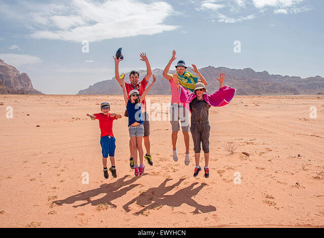 Happy family jumping in the air Wadi Rum, Aqaba, Jordan - Stock Image