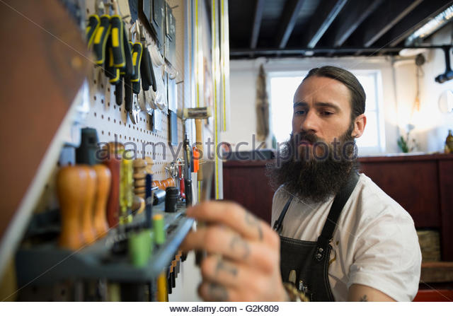 Leather worker selecting tool from wall in workshop - Stock Image
