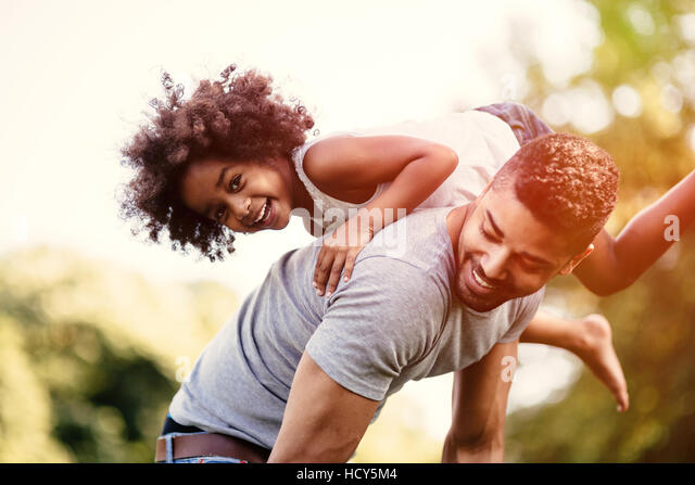 Father carrying daughter on back outdoors - Stock Image