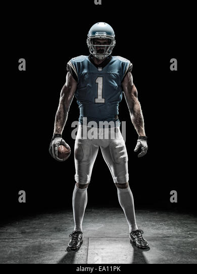 Football player holding ball - Stock Image