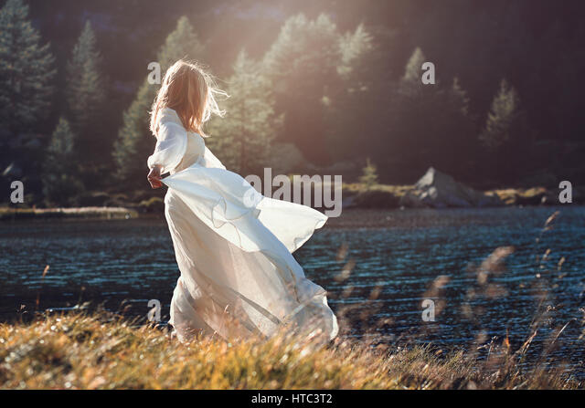 Romantic vintage woman in sunset light. Alpine lake background - Stock-Bilder