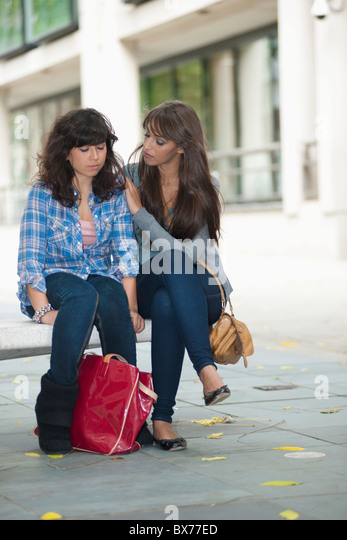 Young female consoling friend - Stock Image