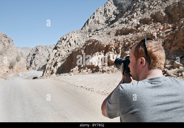 Tourist taking Photograph in Wadi Bih, Oman - Stock Image