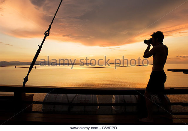 A photographer captures the late afternoon light with a DSLR camera. - Stock Image