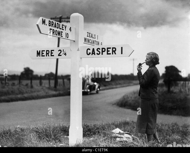 Lady smoking a pipe standing next to road sign post in Wiltshire in the 1930's. - Stock Image