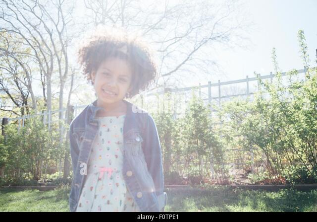 Front view of girl in sunlight, hands behind back, looking at camera smiling - Stock Image