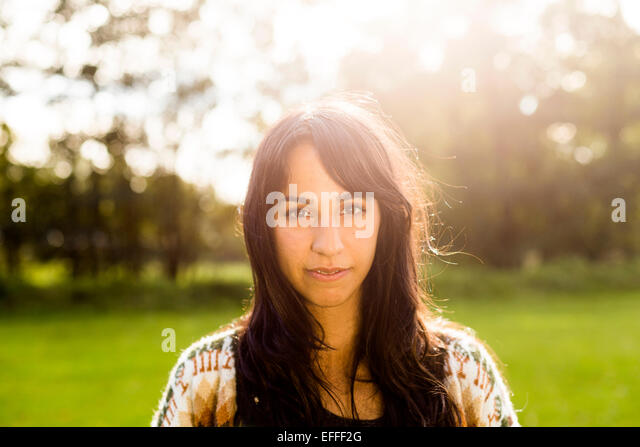 Portrait of beautiful young woman at field - Stock Image