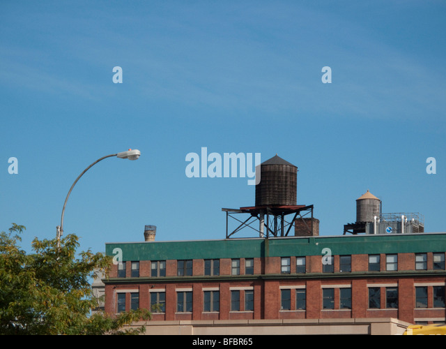 Low rise older industrial building in New York City with typical water tower on the roof. - Stock Image