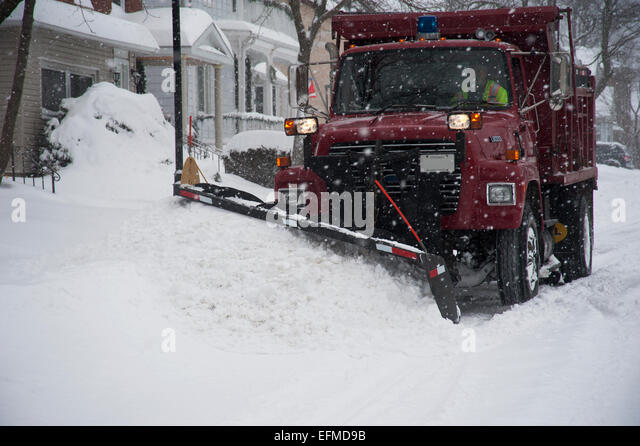 Snow removal truck plowing the road in winter, Gananoque, Ontario, Canada - Stock Image