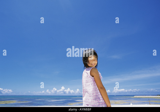 Girl looking back and smiling at the beach - Stock-Bilder