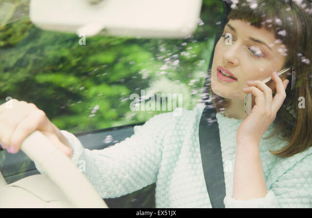 Close up of Teenage Girl Talking on Smartphone whilst Driving - Stock Image
