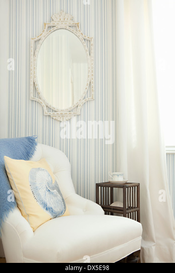 Mirror on striped wall above armchair in blue and white bedroom - Stock Image