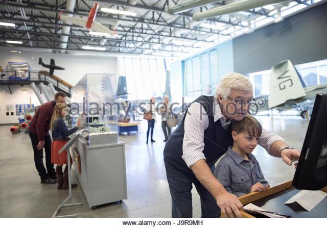 Grandfather and grandson at interactive exhibit in war museum hangar - Stock-Bilder