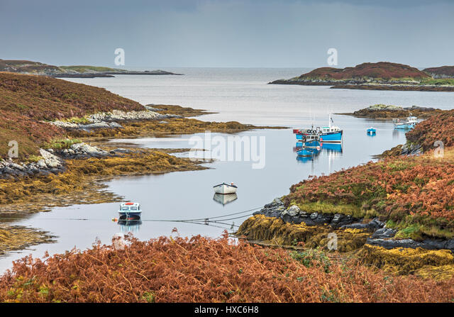 View of fishing boats on tranquil lake, Loch Euphoirt, North Uist, Outer Hebrides - Stock Image