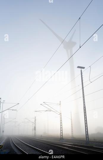 Germany, Hamburg, wind turbine next to railway track in early morning fog - Stock Image