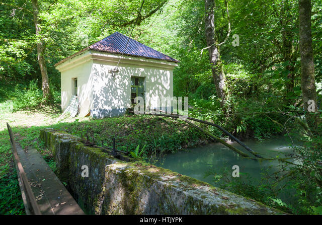 White house with water intake on the shore of a stream at a trout farm in Abkhazia - Stock Image
