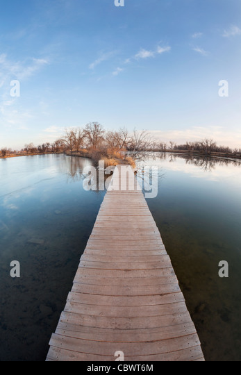 pathway, journey or goal concept - boardwalk and trail across lake and swamp, wide angle fisheye lens perspective - Stock Image