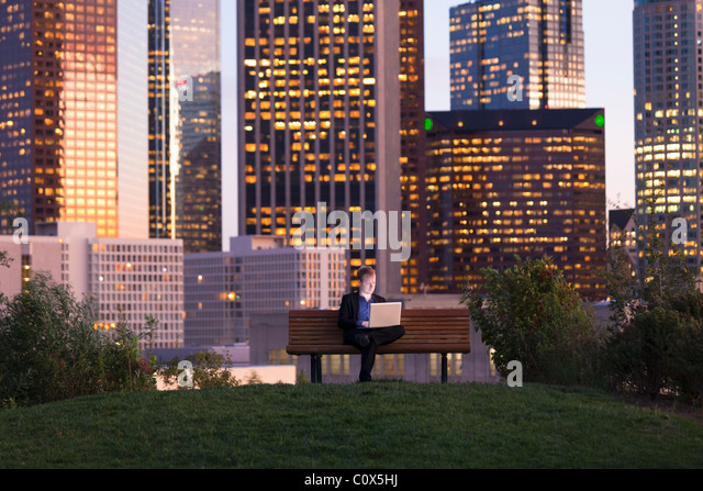 Male sitting on park bench working on laptop computer with Los Angeles city skyline in background at dusk, sunset - Stock-Bilder