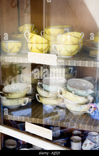 Stacked china and crockery in glass fronted cupboard of 17th century Irish castle - Stock-Bilder