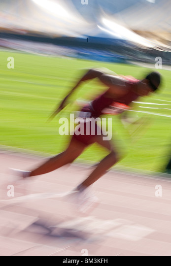 Blurred action of High School boy in the starting block competing at the 2009 Reebok Grand Prix - Stock Image