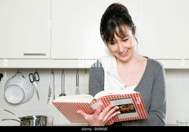 Woman reading cookbook - Stock-Bilder