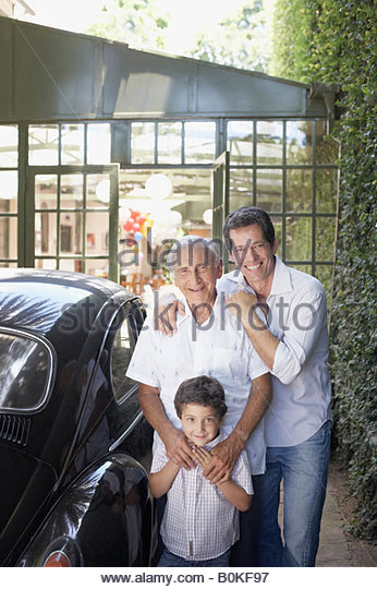 Senior man with man and young boy outdoors standing beside car smiling - Stock-Bilder
