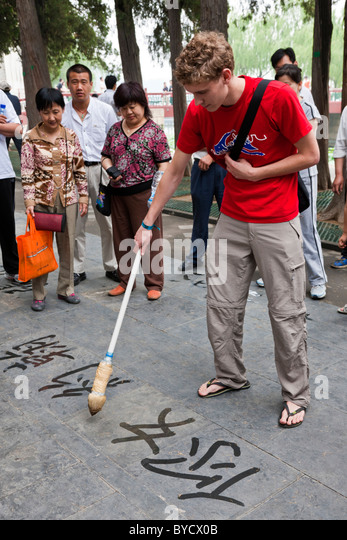 Young English man tourist tries his hand at Street calligraphy in the grounds of the New Summer Palace, Beijing, - Stock Image