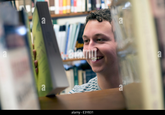 Young man choosing book in library - Stock Image