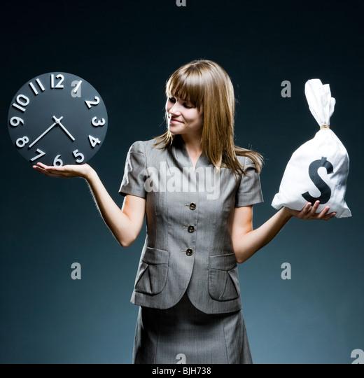 businesswoman weighing time versus money - Stock Image
