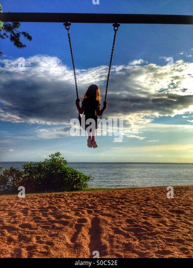 Young girl on a swing at the beach. - Stock-Bilder