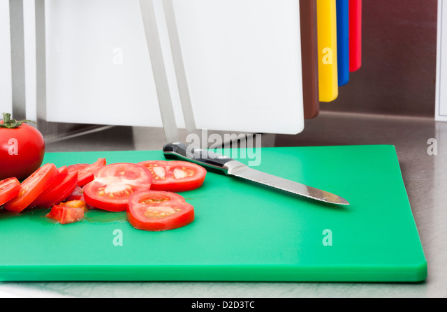 Cut tomatoes Cut tomatoes on the appropriate colour-coded board - Stock Image