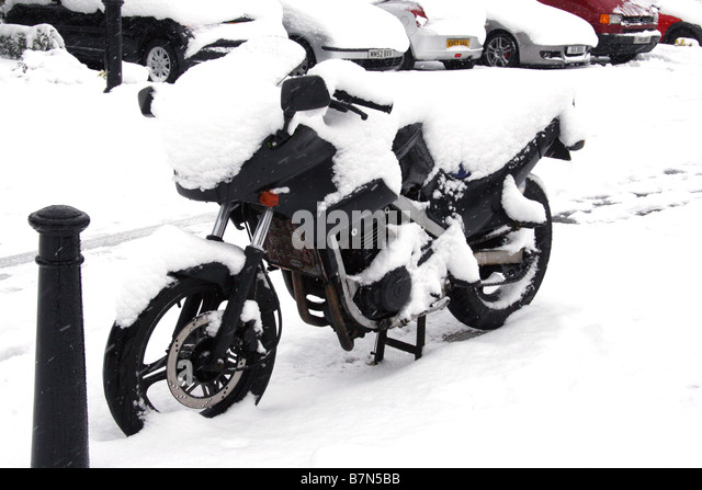 Motorbike covered in snow - Stock Image