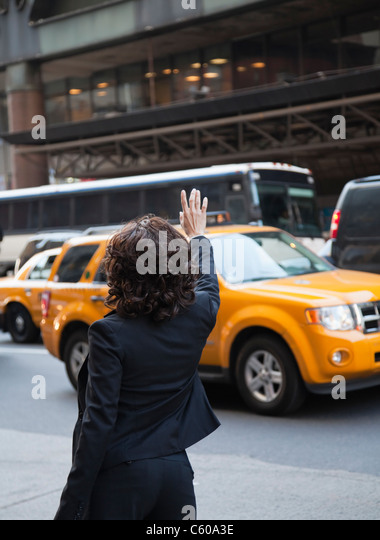 USA, New York, New York City, rear view of woman hailing taxi - Stock Image