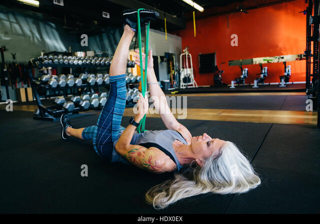 Caucasian woman stretching leg with resistance band - Stock Image