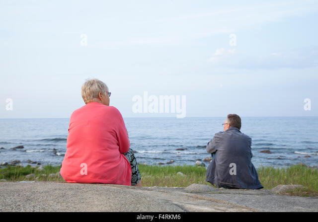 Sweden, Skane, Osterlen, Senior woman and man sitting by Baltic sea - Stock Image