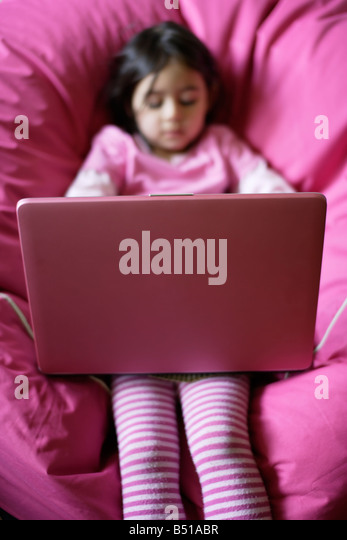 Five year old girl using pink laptop computer sitting on pink beanbag - Stock Image