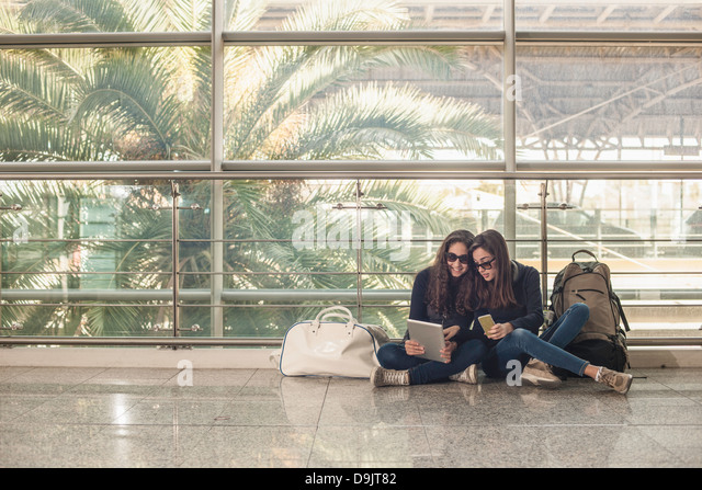 Teenage girls sitting on floor using digital tablet - Stock Image