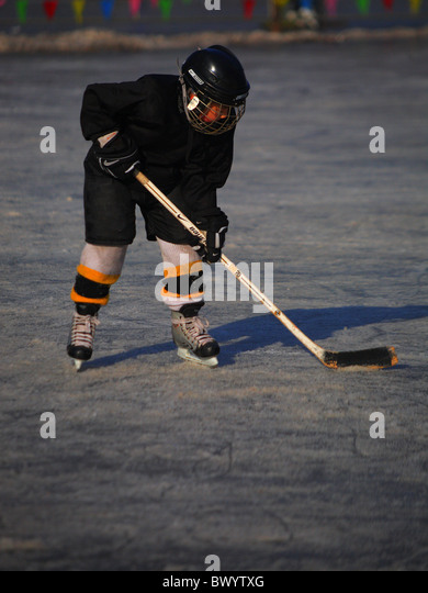 Child playing ice hockey on the frozen surface of Houhai Lake, Beijing, China - Stock Image