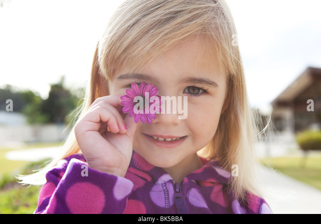 Little girl with purple flower - Stock Image