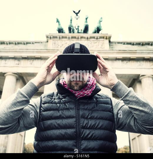 Man wearing VR virtual reality headset at Brandenburg gate in Berlin - Stock-Bilder