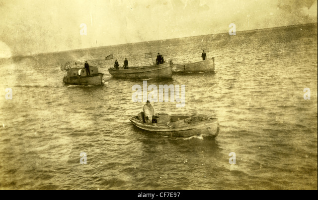 Navy boats with an 1890 or 1889 American Flag with 42 stars move in waters on a lake or river during the late 1800s. - Stock-Bilder