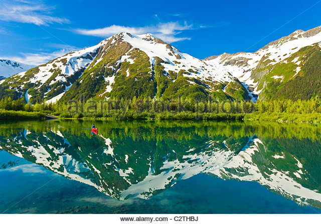 Person canoeing in small lake in Portage Valley of Chugach National Forest during Spring in Southcentral Alaska - Stock Image