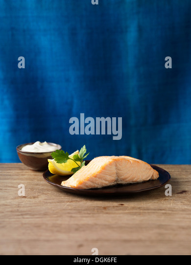 Still life with fresh scottish lochmuir salmon, lemon and parsley - Stock-Bilder