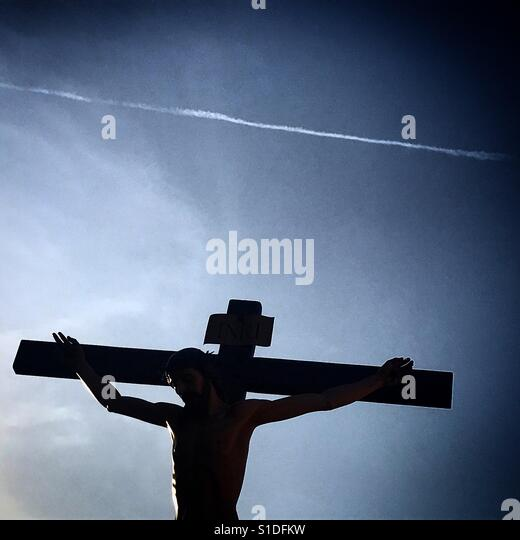 The silhouette of a Christ crucified and a chemtrail during Easter Week in Baeza, Jaen province, Spain - Stock-Bilder