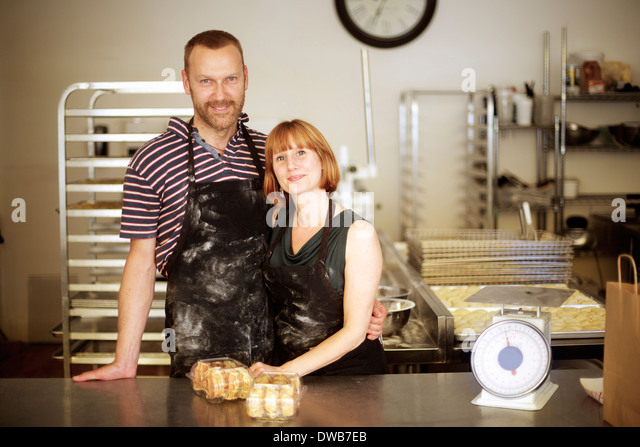 Portrait of baker couple behind kitchen counter - Stock Image