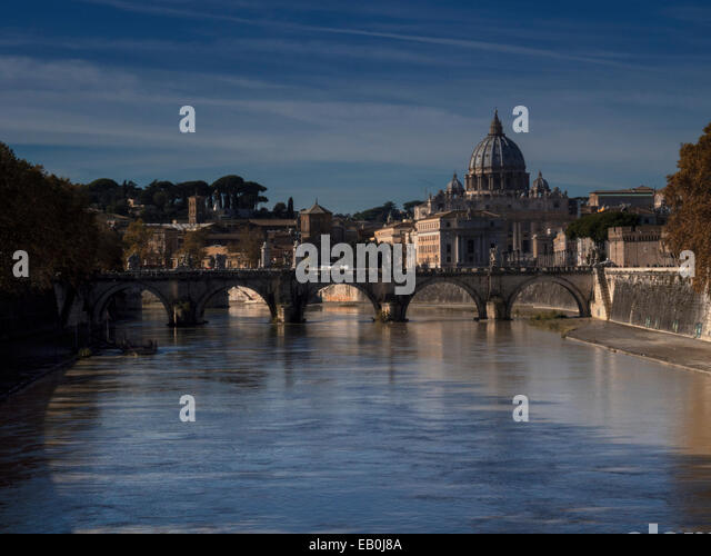 The dome of St Peter's Basilica rises above the River Tiber in the autumnal light, Rome, Italy - Stock Image