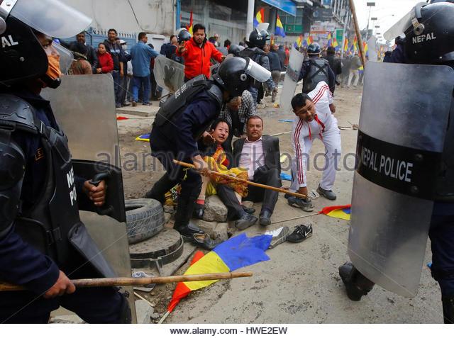 Riot police personnel helps an injured Hindu activist (C) affiliated with Rastriya Prajatantra Party Nepal (RPP - Stock-Bilder